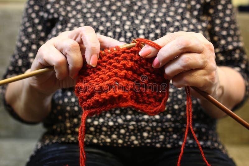 Het bejaarde is bezig geweest met het breien van warme sweaters voor haar grand stock foto's
