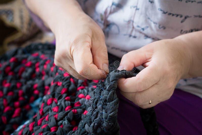 Het bejaarde dame naaien met naald en draad die het handwerk doen stock afbeeldingen