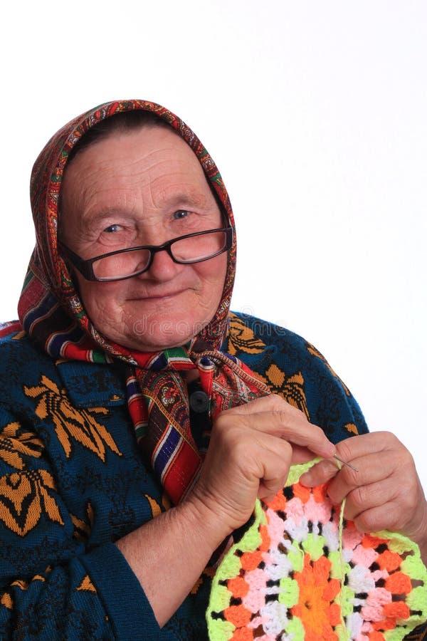 Het bejaarde, die het servet breien stock afbeelding