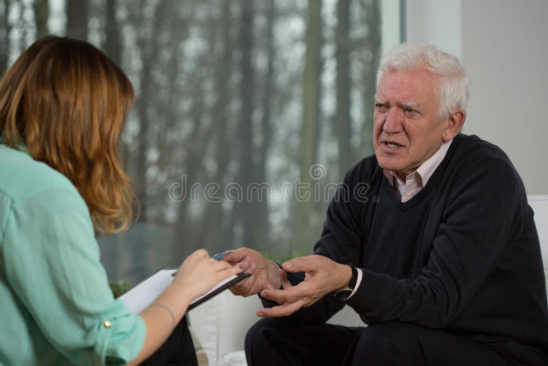 Het bejaarde geduldige spreken met psychotherapist royalty-vrije stock afbeelding