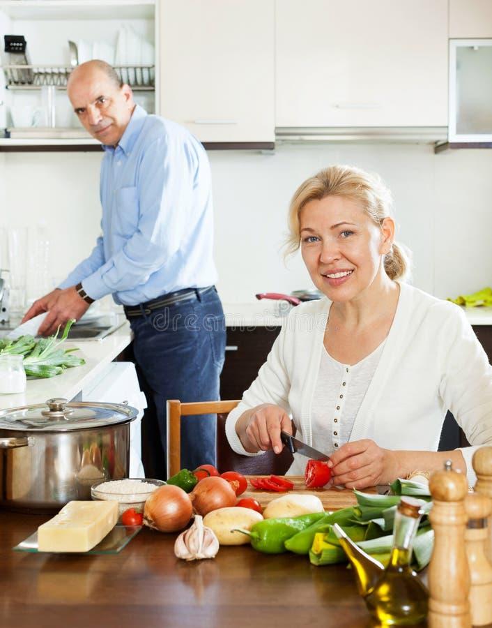 Het bejaarde gelukkige aantrekkelijke het glimlachen paar koken stock fotografie