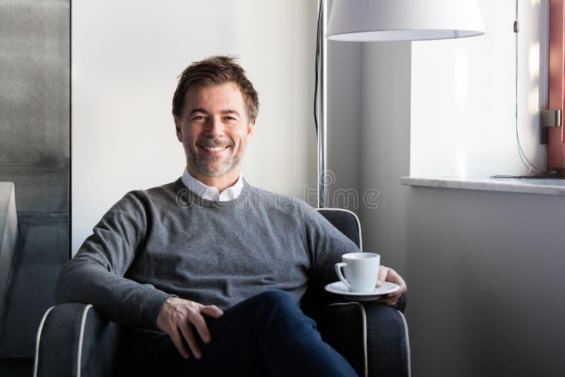 Het bejaarde het glimlachen mens ontspannen in een bank met een kop thee royalty-vrije stock fotografie