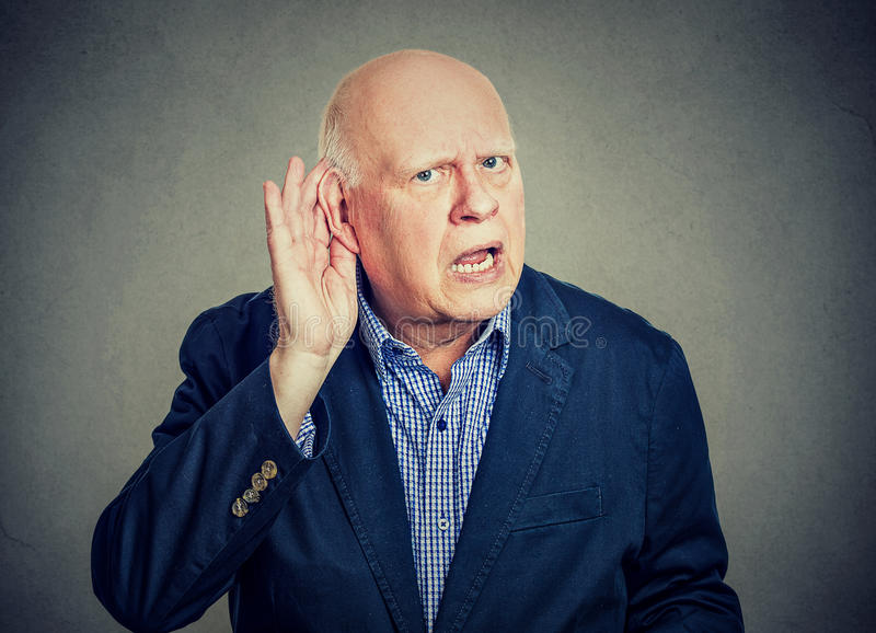 Het bejaarde houdt zijn hand dichtbij oor en het luisteren stock foto's