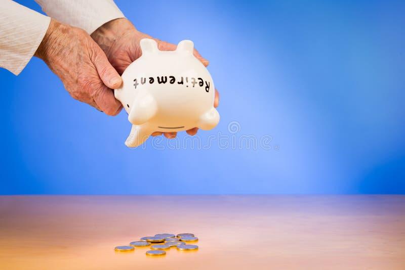 Het bejaarde maakt haar piggybank met besparingenpensionering leeg stock foto