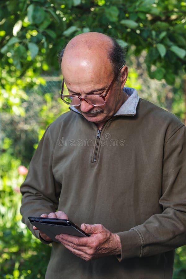 Het bejaarde met een kaal hoofd, de snor en de glazen leren om tablet te behandelen royalty-vrije stock fotografie