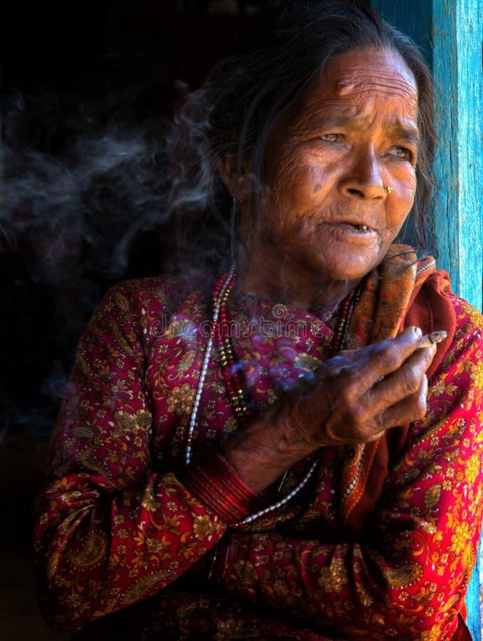 Het bejaarde Nepali-vrouw roken stock afbeeldingen