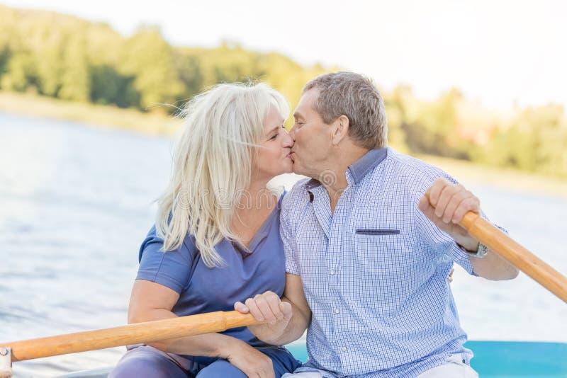 Het bejaarde paar kussen op een boot royalty-vrije stock foto's