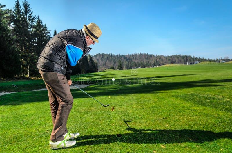 Het bejaarde speelt golf stock afbeeldingen