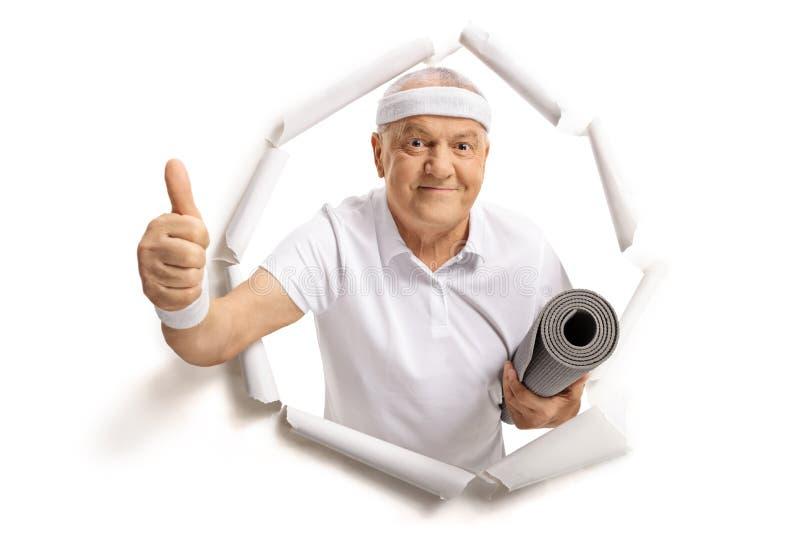 Het bejaarde sportman breken door document en het maken van een duim op s stock foto