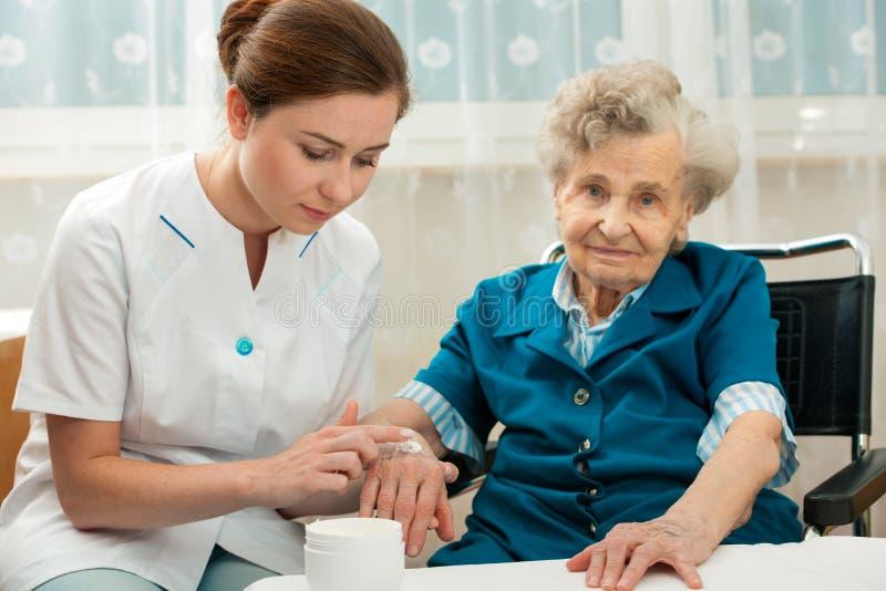 Het bejaarde wordt thuis bijgestaan door verpleegster stock foto