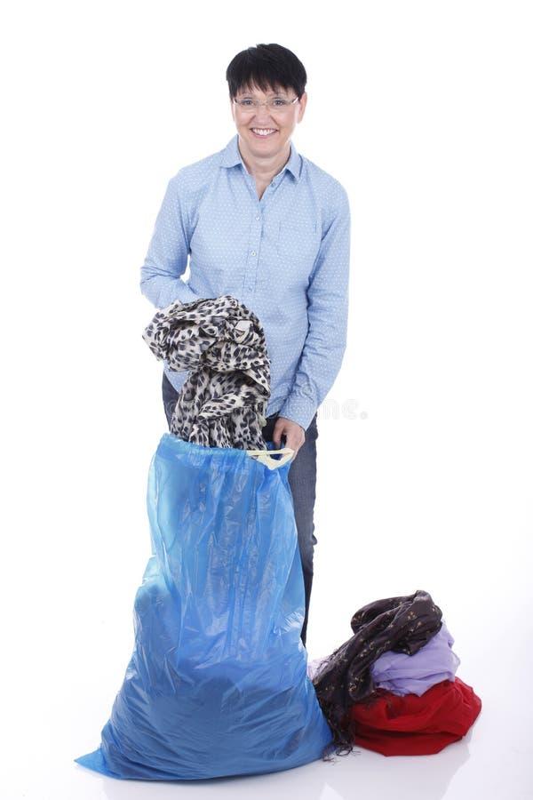 Het bejaarde zet gebruikte kleren in een grote zak stock fotografie