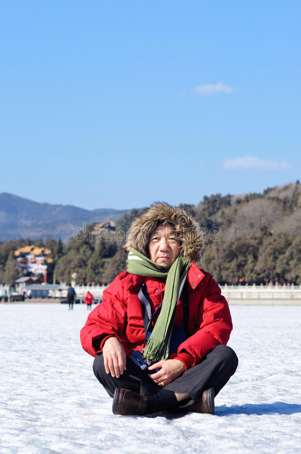 Het bejaarde zit op sneeuw stock afbeelding