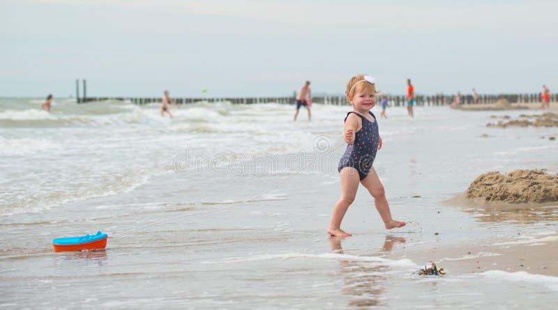 Het bekijken de rug van een babymeisje op het strand met een bootstuk speelgoed royalty-vrije stock fotografie