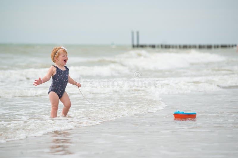 Het bekijken de rug van een babymeisje op het strand met een bootstuk speelgoed stock foto's