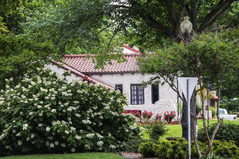 Het bekijken door bloeiende struiken en bomen het zuidwestelijke huis van de adobestijl met betegeld dak in mooie de lentebuurt m stock fotografie