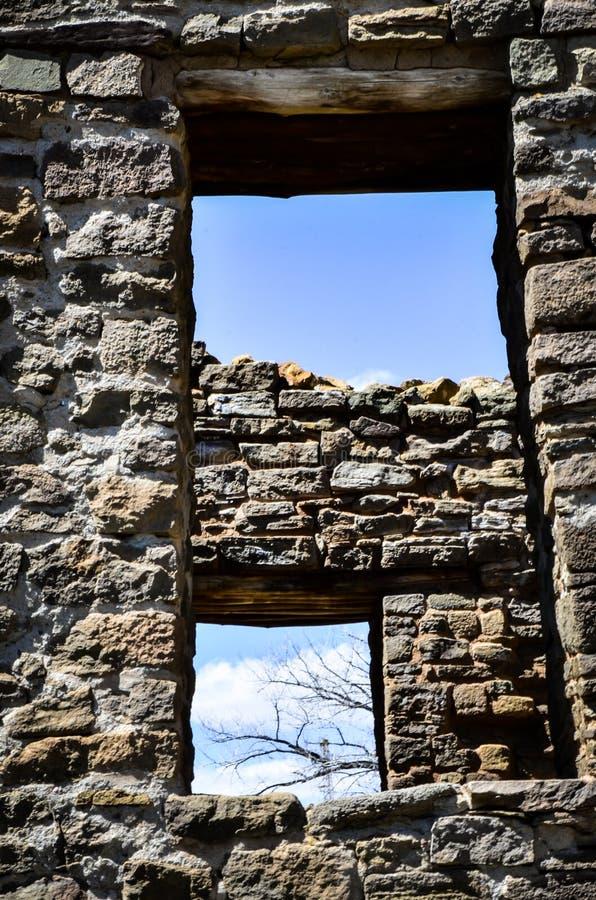 Het bekijken door Oude Vensters een Blauwe Hemel met Naakte Takken en Wolken stock afbeeldingen