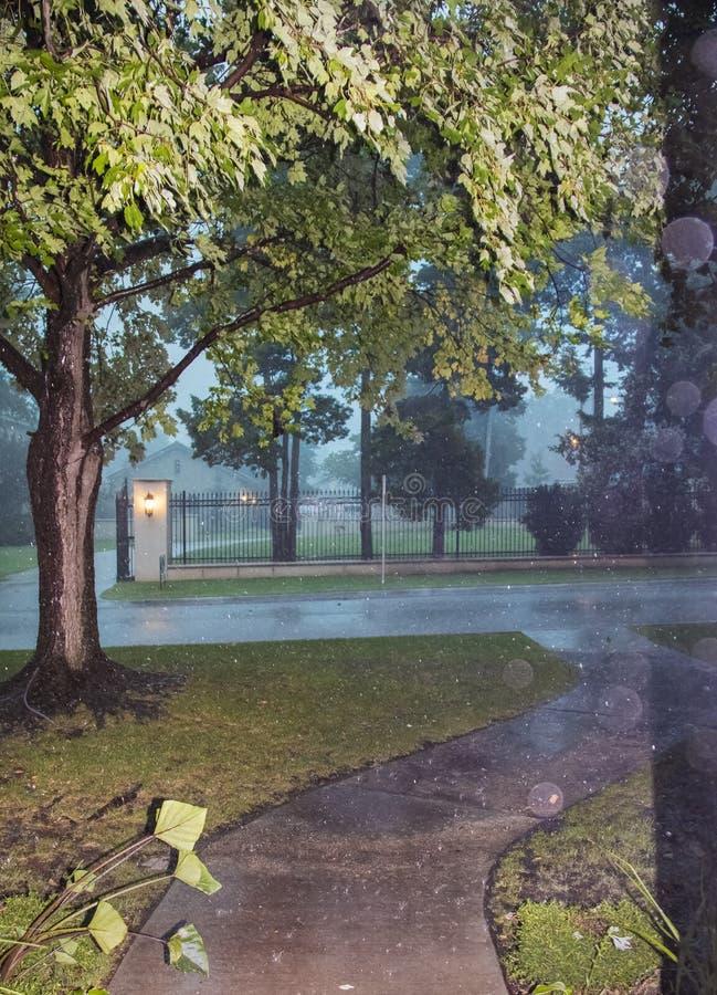 Het bekijken uit straat en omheining en bomen in stedelijke buurt tijdens een zware stortbui op stormachtige donkere dag met zich royalty-vrije stock foto