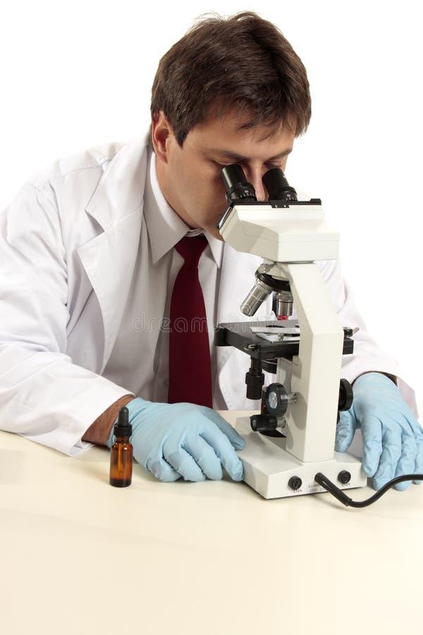 Het bekijken van de onderzoeker substantie onder microscoop stock afbeelding