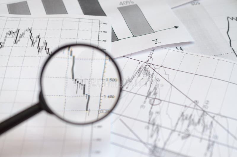 Het bekijken van forex grafieken door een vergrootglas stock afbeelding