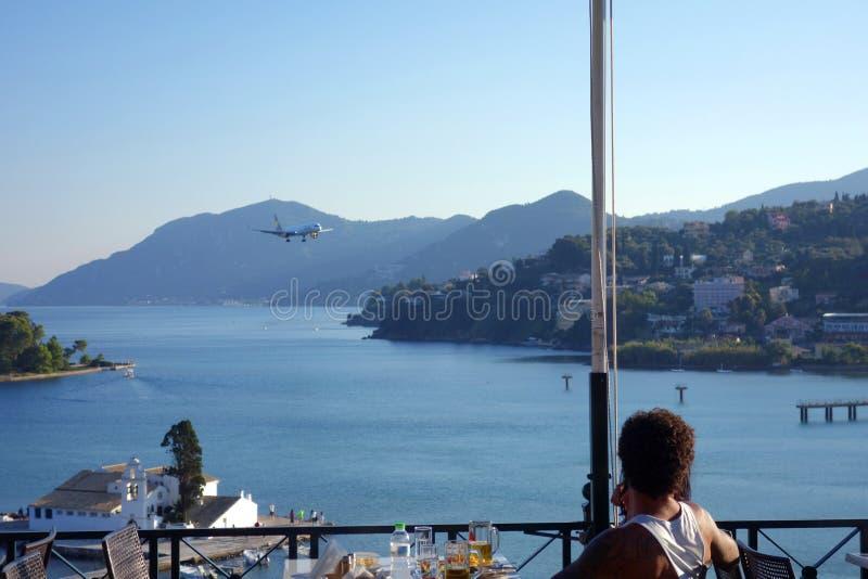 Het bekijken vliegtuig bij het restaurant van Korfu stock fotografie
