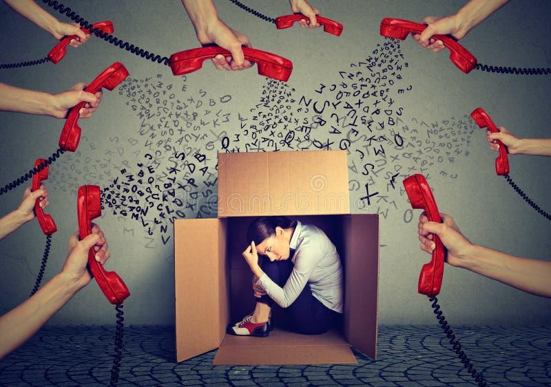 Het beklemtoonde bedrijfsdievrouw verbergen in een doos door vele telefoongesprekken en boodschappen wordt overweldigd zou moeten stock foto's