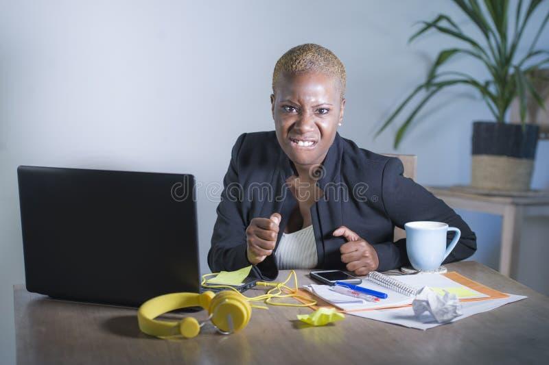 Het beklemtoonde en gefrustreerde afro Amerikaanse zwarte werken binnen overweldigd en verstoord bij bureaulaptop computerbureau  royalty-vrije stock foto