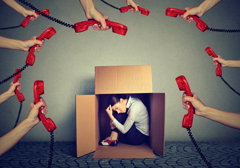 Het beklemtoonde jonge bedrijfsvrouwenzitting verbergen in een doos die door teveel telefoongesprekken en boodschappen wordt over royalty-vrije stock fotografie