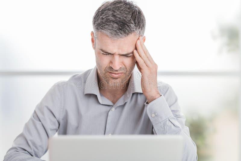 Het beklemtoonde zakenman werken bij bureau en het hebben van een hoofdpijn, raakt hij zijn tempels stock afbeeldingen