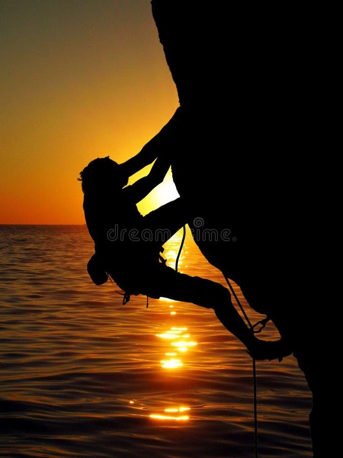Het beklimmen in de zonsondergang stock afbeeldingen
