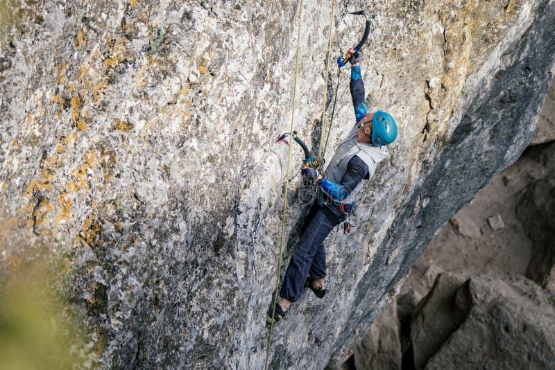 Het beklimmen van de mens op een rots royalty-vrije stock afbeeldingen