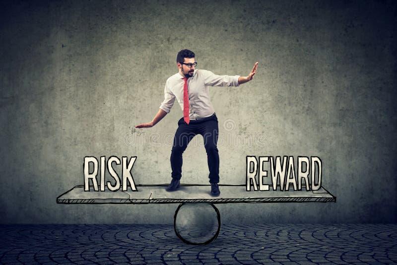 Het bekwame jonge bedrijfsmens in evenwicht brengen tussen beloning en risico stock foto