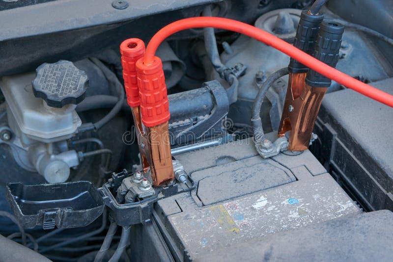 Het belasten van automobiele batterij met de kabels van een andere autoverbindingsdraad bij de winter stock afbeelding