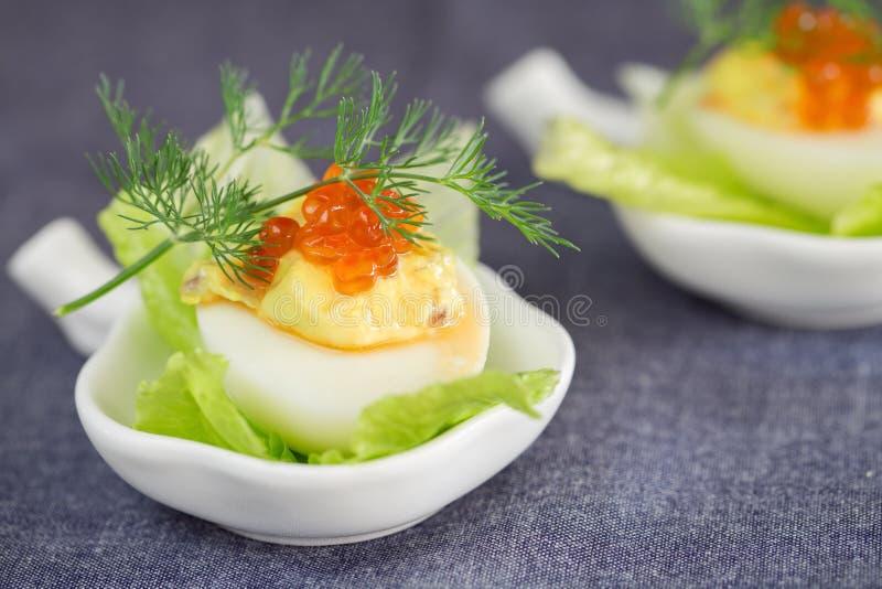Het bemande eivoorgerecht met rode kaviaar versiert en dilledecoratio stock foto