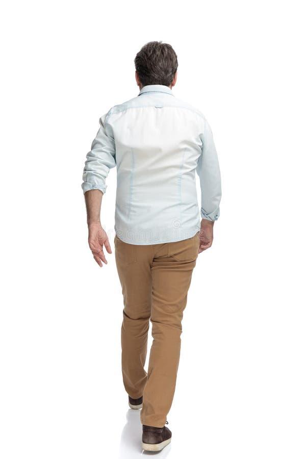 Het bepaalde toevallige mens haastig lopen vooruit stock foto