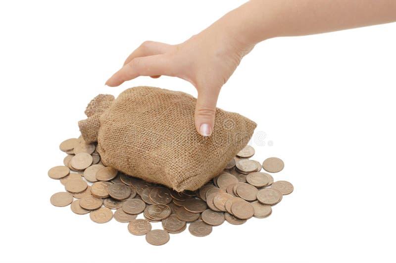 Het bereik van de hand voor zakken met muntstukken stock afbeelding