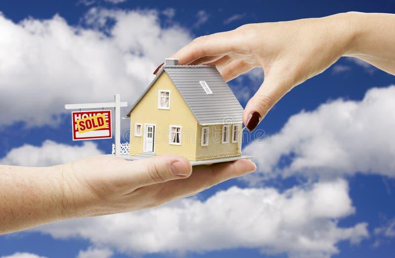 Het bereiken voor een Huis met het Verkochte Teken van Onroerende goederen stock foto