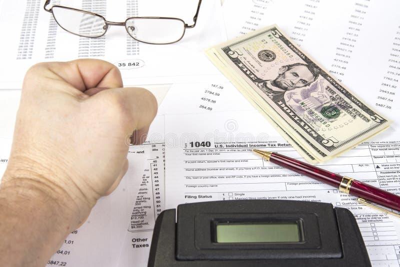 Het berekenen aantallen voor inkomensbelastingaangifte met pen, glazen en calculator stock foto