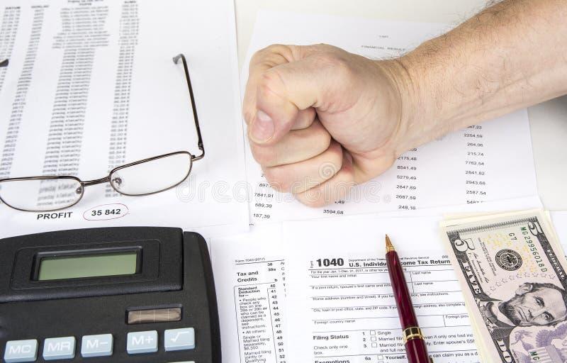 Het berekenen aantallen voor inkomensbelastingaangifte met pen, glazen en calculator stock afbeeldingen