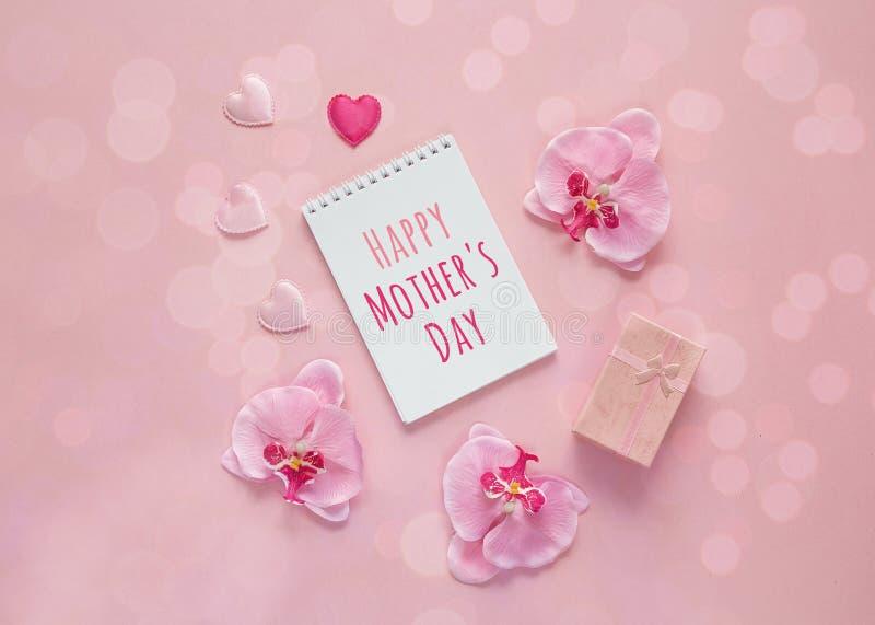 Het bericht van de moedersdag met giftvakje, orchideebloemen en harten  royalty-vrije stock foto