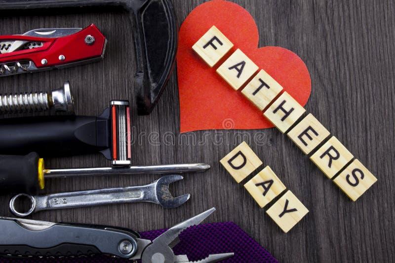 Het bericht van de vadersdag op een houten die achtergrond met reeks hulpmiddelen en banden, door kabel wordt gescheiden stock fotografie