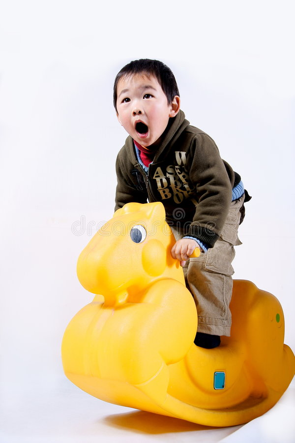 Het berijden van de jongen stuk speelgoed paard stock afbeeldingen