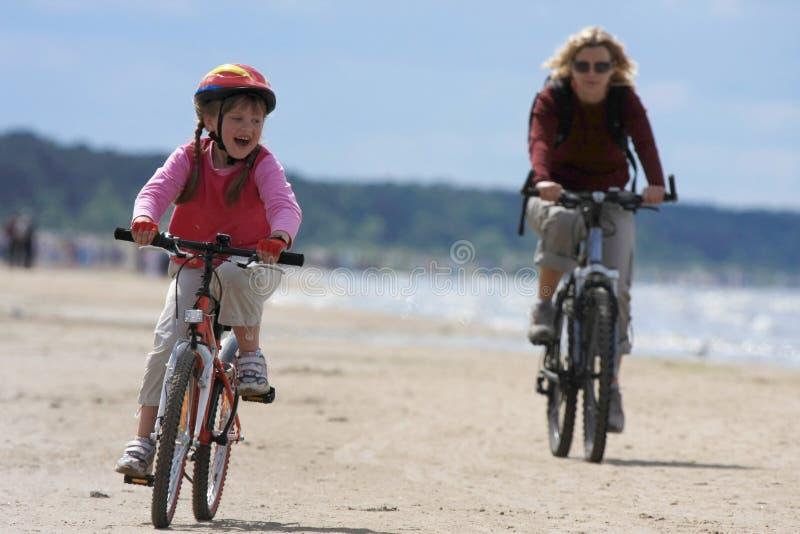 Het berijden van de moeder en van de dochter langs het strand royalty-vrije stock foto's