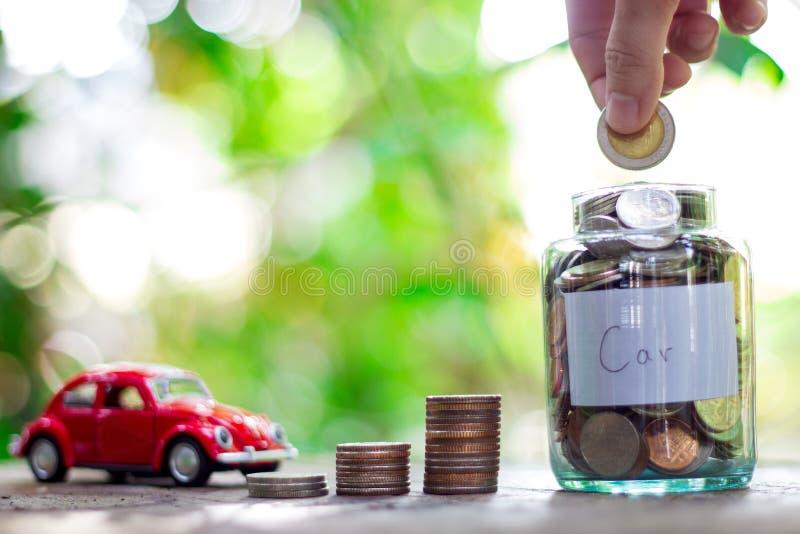 Het besparingsgeld in een glasfles, het doel moet een auto kopen Het geldconcept van de besparing stock afbeeldingen