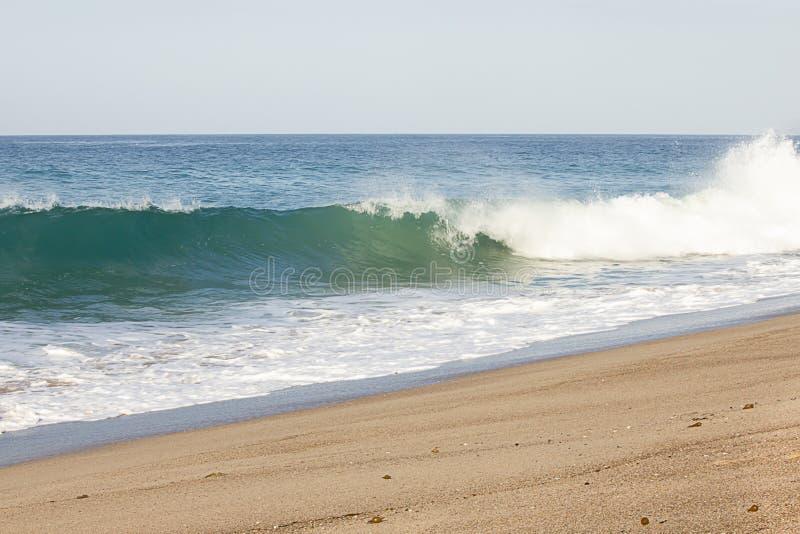 Het bespatten golf het breken van zwellende golf in schuim van terugslag op zandig strand stock fotografie
