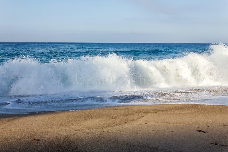 Het bespatten van brekende schuimende golf op zandig strand met terugslag stock fotografie