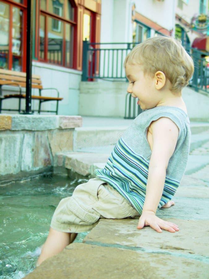 Het bespatten van de jongen in fontein royalty-vrije stock afbeeldingen
