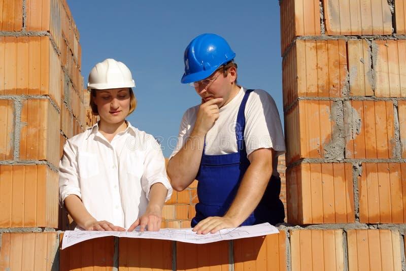 Het bespreken van de bouwplannen stock afbeeldingen
