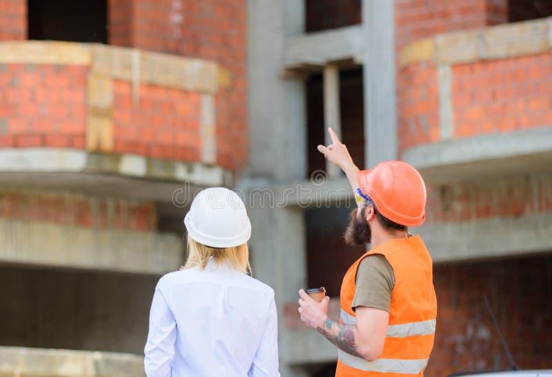 Het bespreken van plan De de vrouweningenieur en bouwer communiceren bij bouwwerf Verband tussen bouwcliënten royalty-vrije stock afbeeldingen