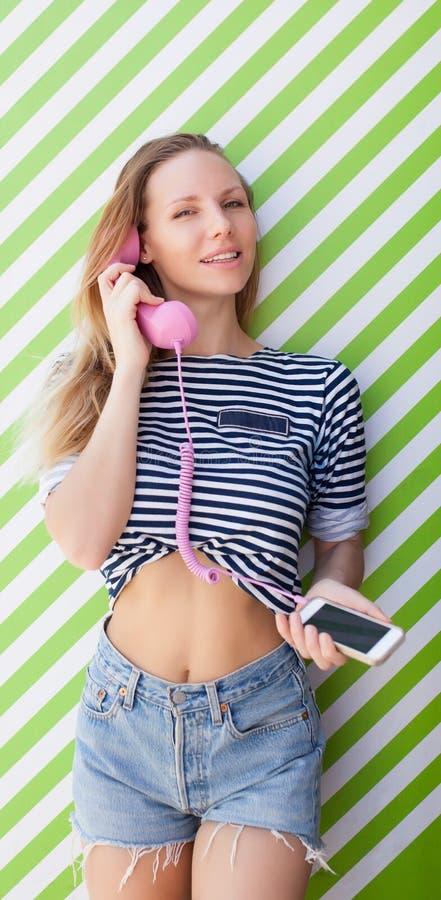 Het beste levensstijlportret van meisjes die modieuze heldere mariene uitrustingen, denimborrels dragen Meisje die op de telefoon royalty-vrije stock fotografie