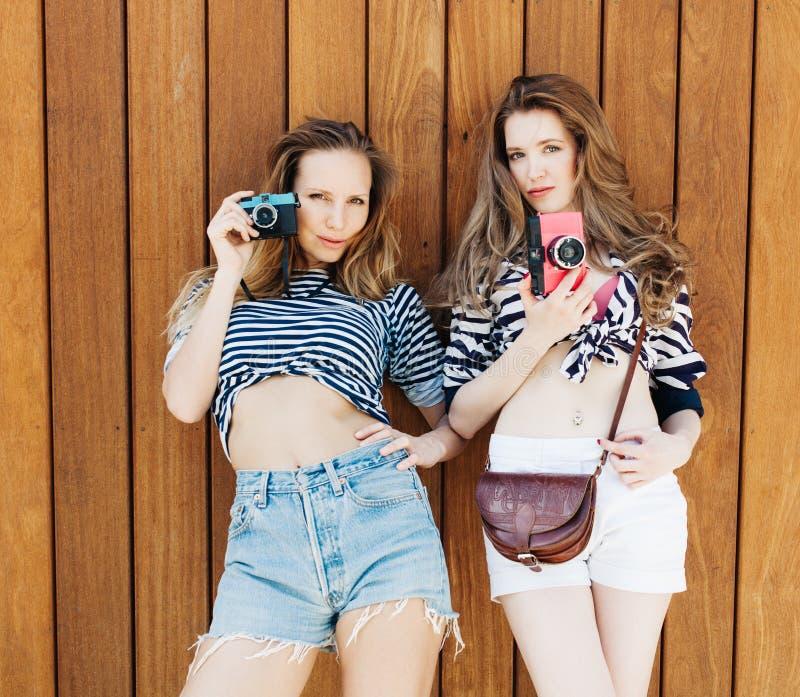 Het beste levensstijlportret van twee beste vriendenmeisjes die modieuze heldere uitrustingen, denimborrels en uitstekende camera stock afbeelding
